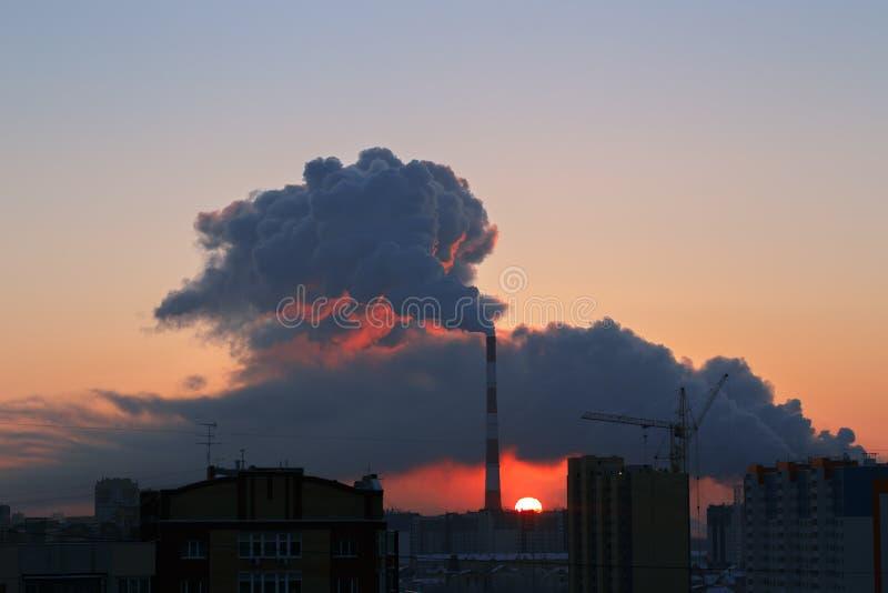 Paysage urbain au lever de soleil avec le tuyau de tabagisme photographie stock