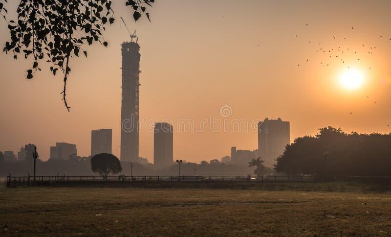 Paysage urbain au lever de soleil un matin brumeux d'hiver comme vu de Kolkata maidan photographie stock libre de droits