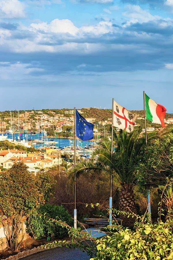 Paysage urbain avec les yachts de luxe de drapeaux à la marina à Porto Cervo image stock