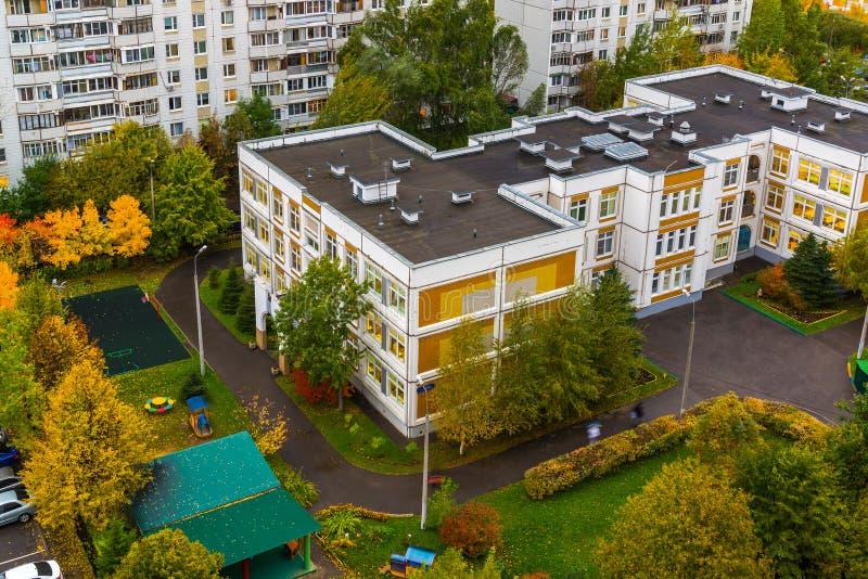 Paysage urbain dans le secteur de sommeil dans la chute avec le jardin d'enfants et l'école à Moscou, Rusia photographie stock