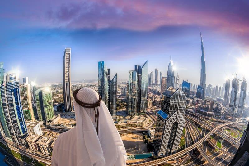 Paysage urbain de observation d'homme Arabe de Dubaï avec l'architecture futuriste moderne aux Emirats Arabes Unis images stock
