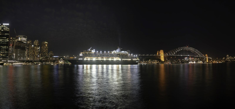 Paysage urbain de panorama : Vue merveilleuse de nuit de ville et de bateau de croisière colorés près de pont de port à Sydney, A images stock