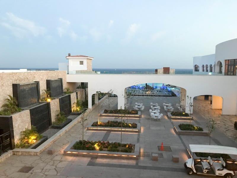 Paysage urbain tropical avec vue sur la mer et grands bâtiments blancs avec un pont, une voûte, des lits de fleur et des plantes  image libre de droits