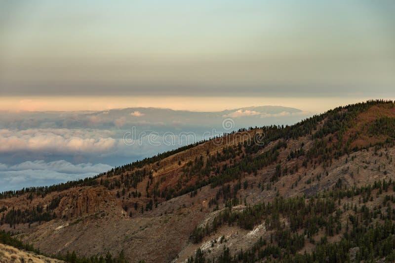 Paysage volcanique de Tenerife avec vue à La Palma à 100 km au-dessus de l'océan Point de montagne au-dessus des nuages au clair photo libre de droits