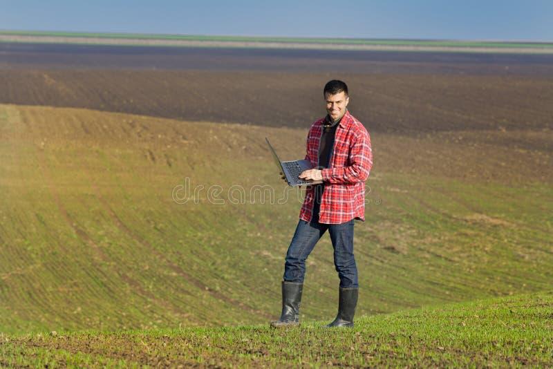 Paysan avec l'ordinateur portable dans les jeunes plantes photographie stock