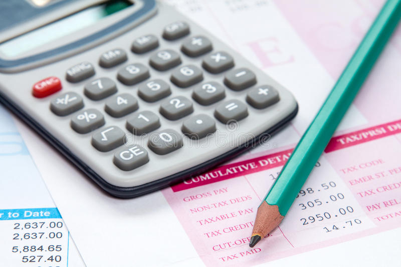 Payslip with calculator and pencil stock photography