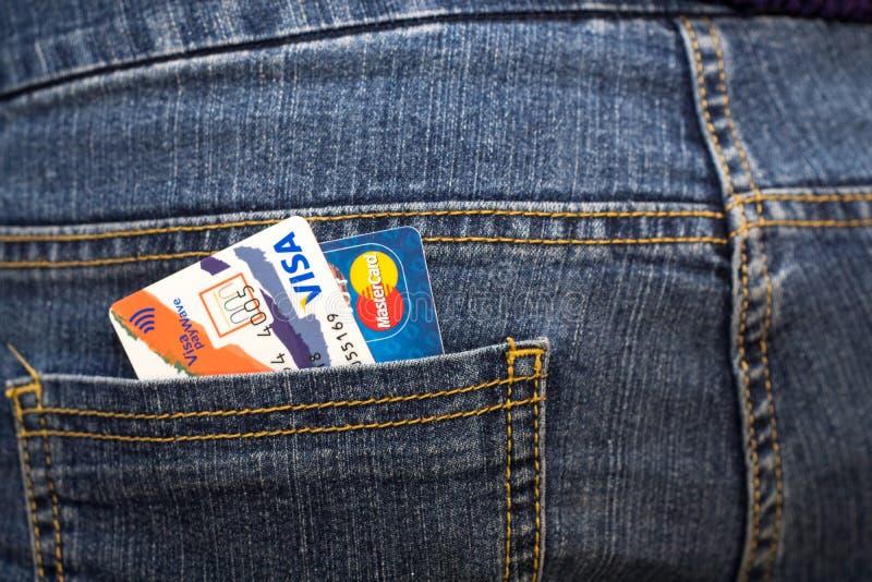 PayWave y Mastercard de la visa de las tarjetas de crédito en el bolsillo trasero de vaqueros imagen de archivo