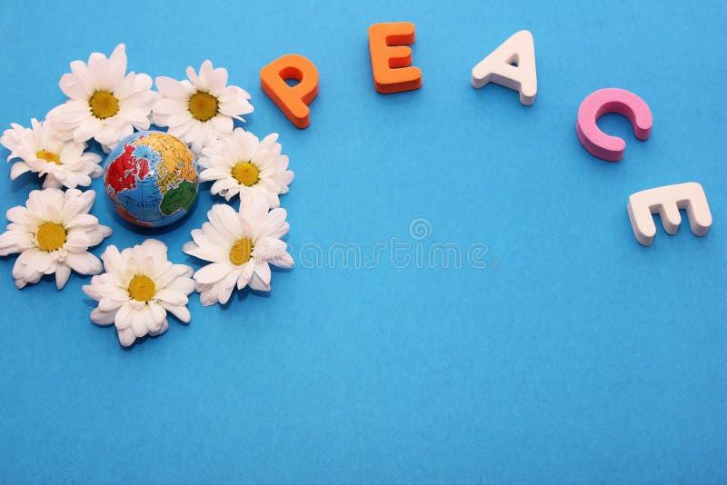 A PAZ da palavra fez por letras perto de pouca figura de um globo cercado por flores dos cris?ntemos brancos Copie o espa?o fotografia de stock