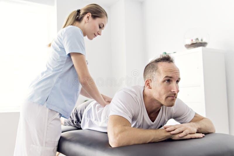 Paziente alla fisioterapia che fa gli esercizi fisici con il suo terapista fotografia stock
