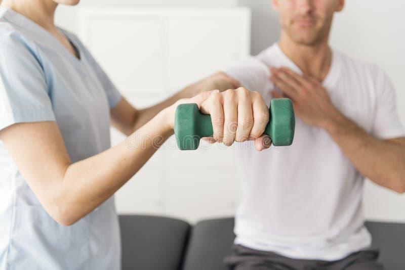 Paziente alla fisioterapia che fa gli esercizi fisici con il suo terapista immagine stock libera da diritti