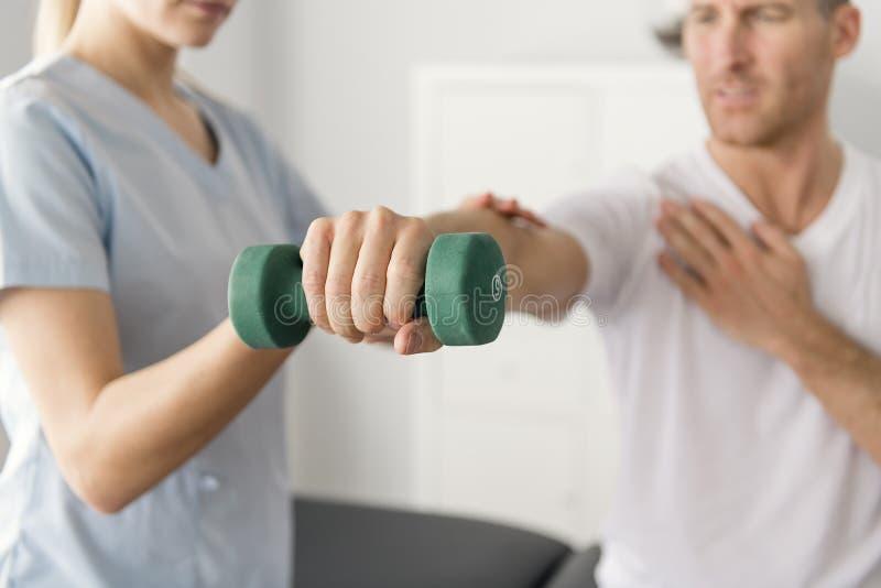 Paziente alla fisioterapia che fa gli esercizi fisici con il suo terapista fotografie stock libere da diritti