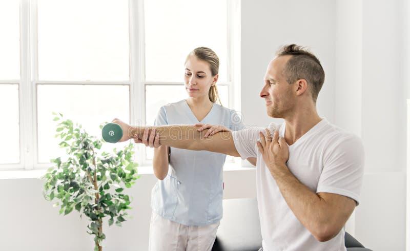 Paziente alla fisioterapia che fa gli esercizi fisici con il suo terapista fotografia stock libera da diritti