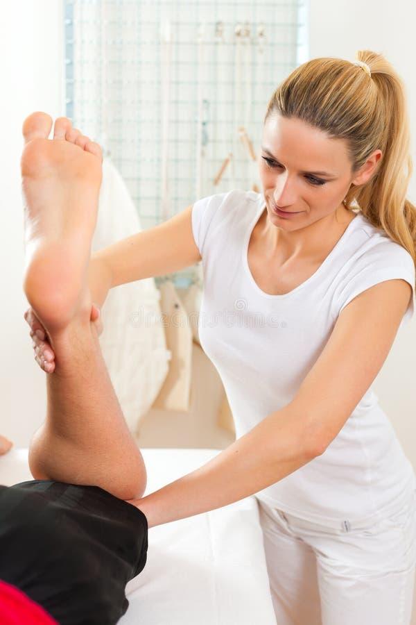 Paziente alla fisioterapia che fa terapia fisica immagini stock
