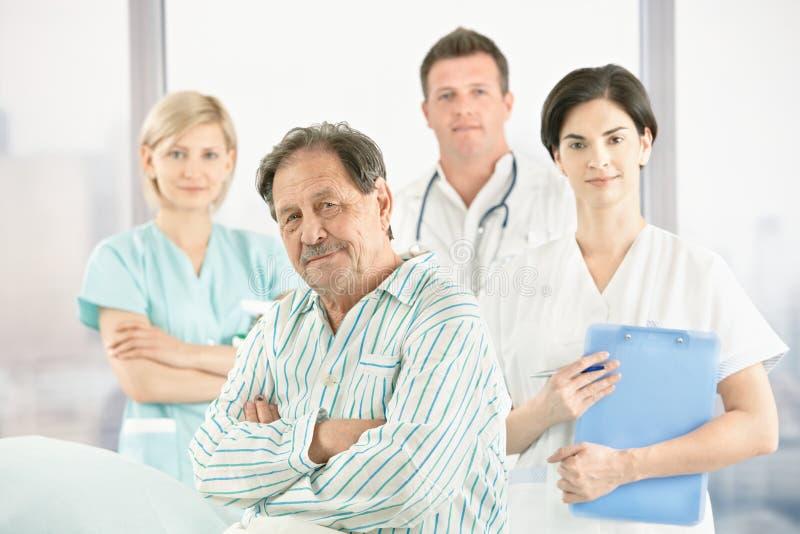 Paziente anziano con i medici e l'infermiera immagine stock
