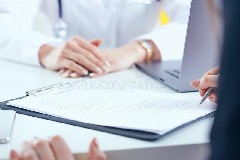 Paziente che firma contratto medico Medico femminile spiega come riempire la forma medica fotografia stock libera da diritti