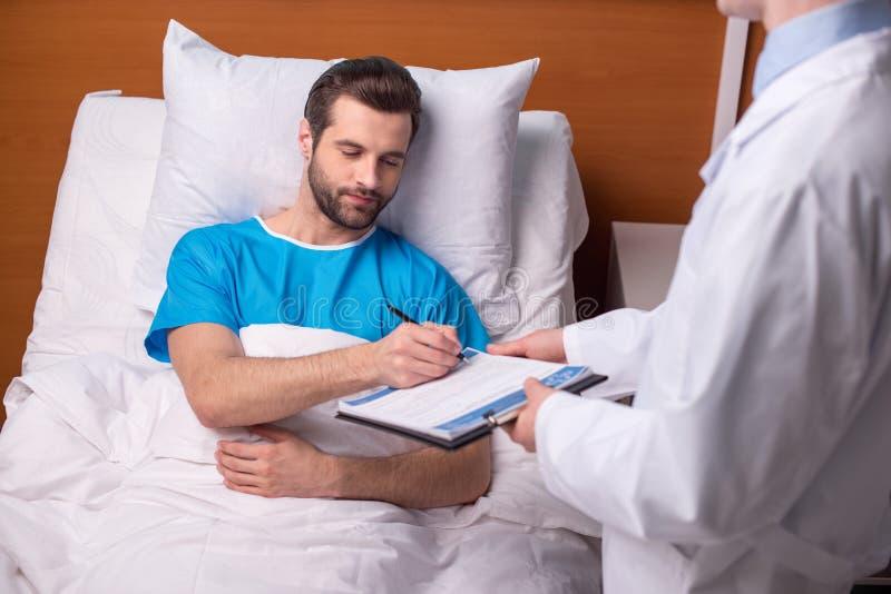 Paziente che firma documento medico fotografia stock