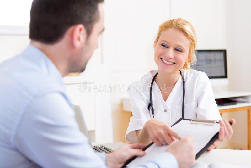 Paziente che firma il documento di giovane medico attraente immagine stock