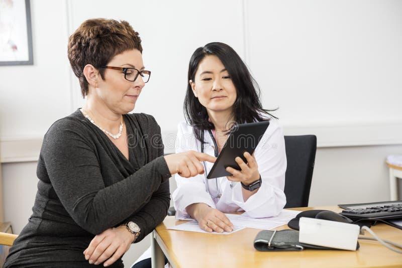 Paziente che indica alla compressa di Digital tenuta da medico fotografie stock libere da diritti