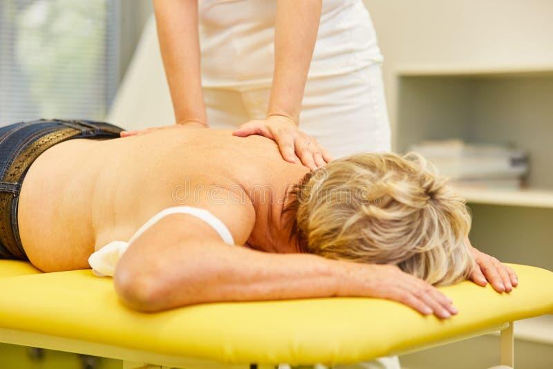 Paziente con il massaggio posteriore in fisioterapia immagini stock