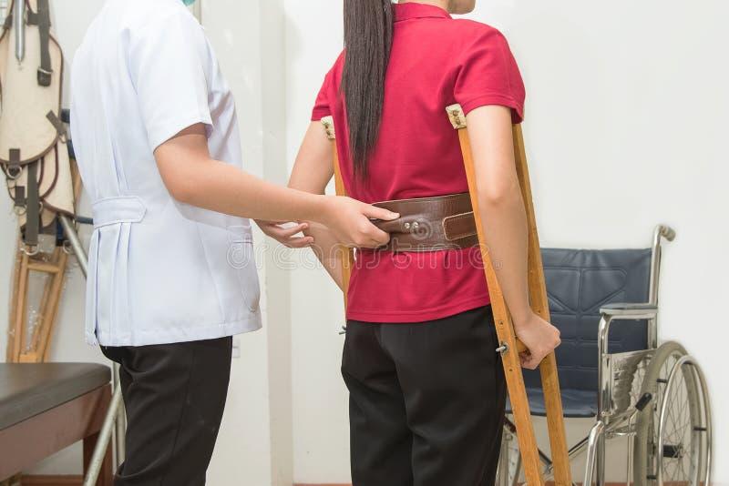 Paziente d'aiuto del terapista fisico da camminare facendo uso delle grucce fotografia stock