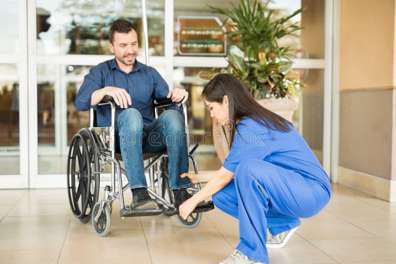 Paziente d'aiuto dell'infermiere in una sedia a rotelle immagini stock libere da diritti
