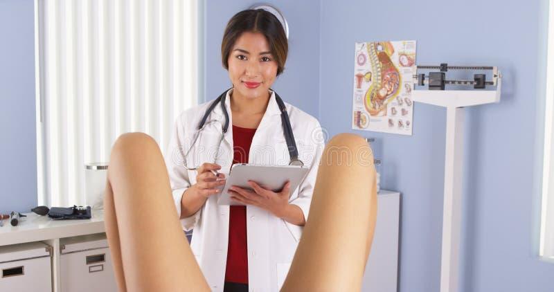 Paziente d'esame asiatico di OBGYN nella stanza dell'esame dell'ospedale immagini stock