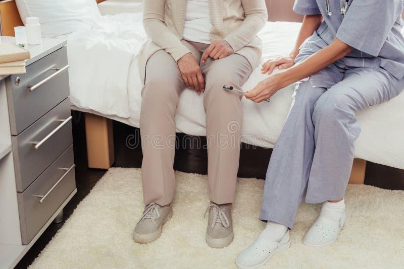 paziente d'esame dell'infermiere con il martello riflesso immagine stock