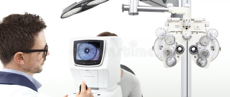 Paziente d'esame di vista dell'optometrista nell'ufficio dell'ottico fotografia stock