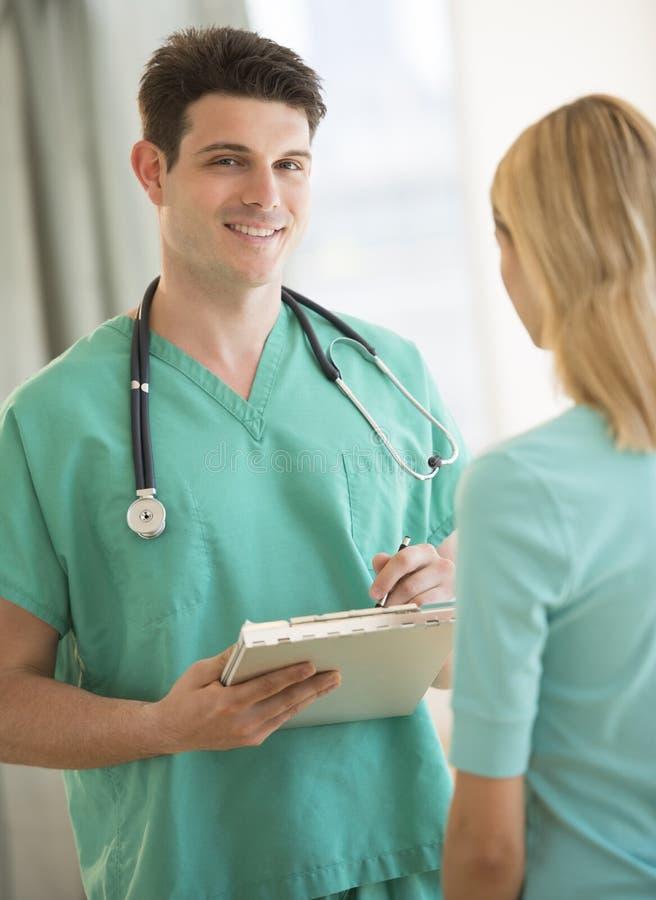 Paziente del dottore Holding Clipboard With che sta nella priorità alta a immagini stock libere da diritti