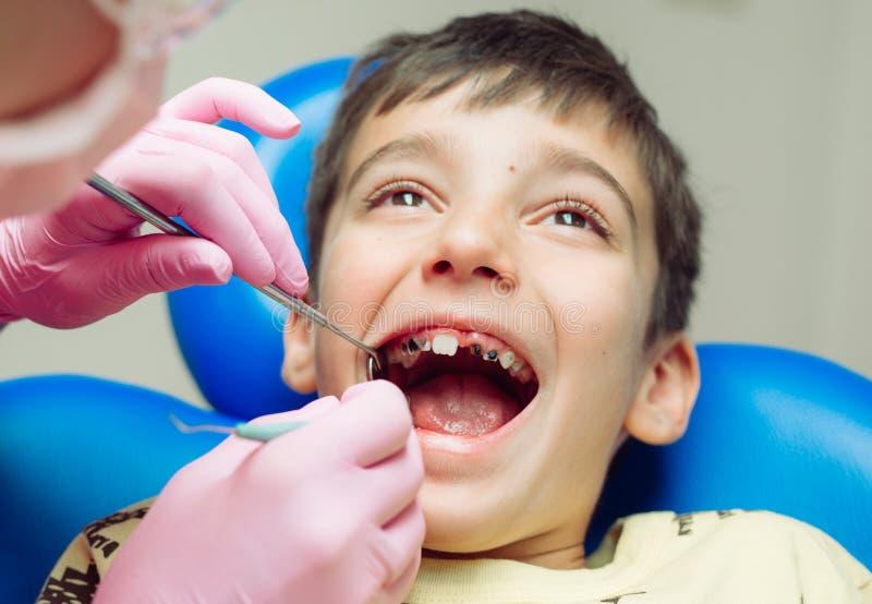 Paziente del ragazzo dell'adolescente al ragazzo del dentista A con i denti di problema che si siedono in una sedia dentaria fotografia stock