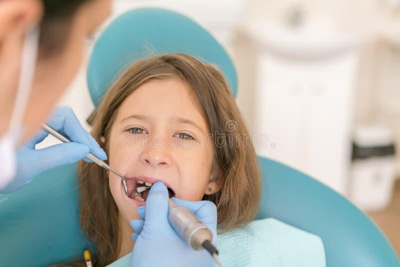 Paziente della bambina e del dentista Primo piano della bambina graziosa che apre la sua bocca ampia durante l'ispezione della ca fotografia stock