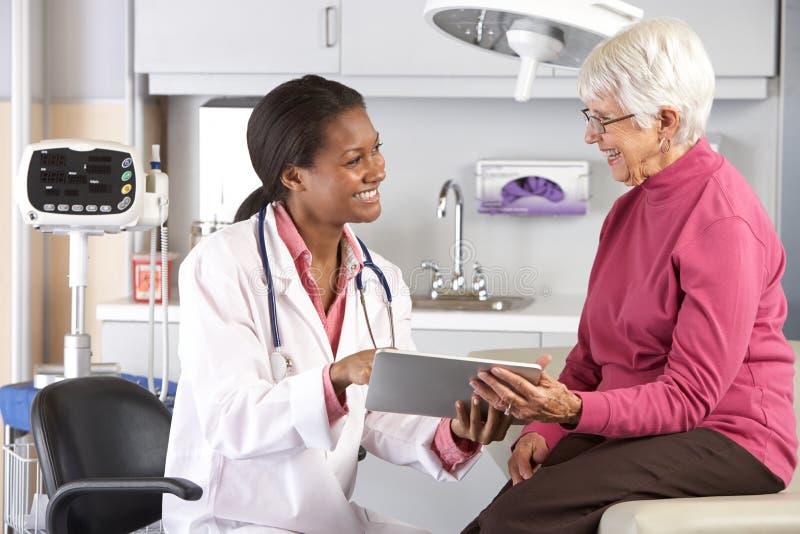 Paziente della femmina del dottore Discussing Records With Senior fotografia stock libera da diritti