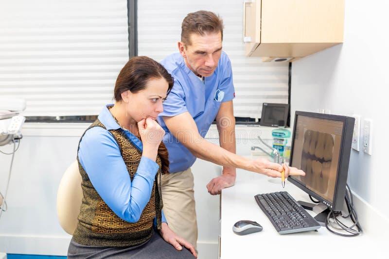 Paziente di rappresentazione del dentista i suoi raggi x dei denti discussione delle edizioni immagini stock