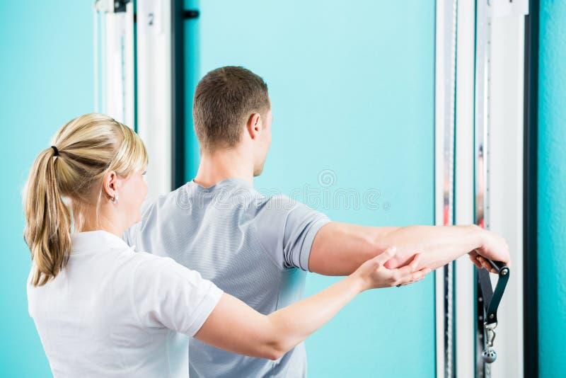 Paziente excercising del fisioterapista in pratica fotografia stock