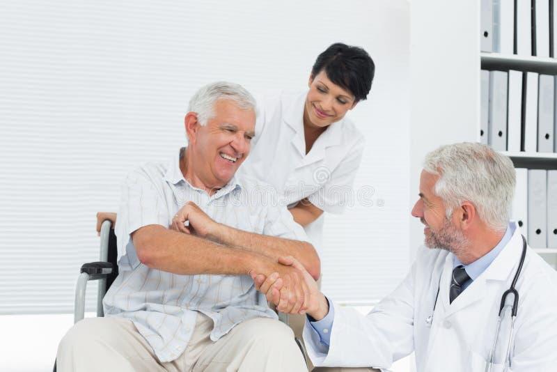 Paziente felice e medico senior che stringono le mani fotografia stock