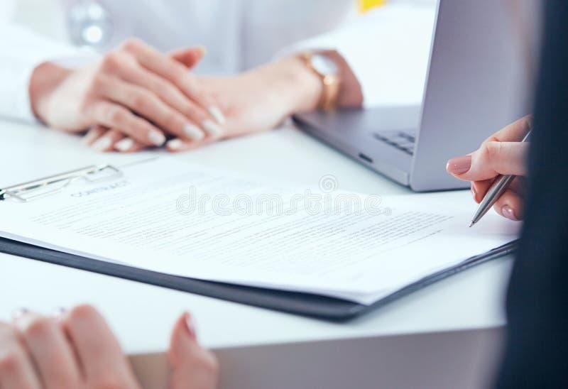 Paziente femminile che firma contratto medico Medico femminile spiega come riempire la forma medica immagini stock libere da diritti