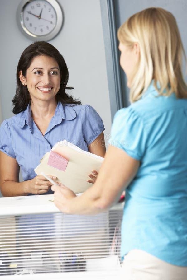 Paziente femminile con la stanza di In Doctors Waiting del receptionist fotografia stock libera da diritti
