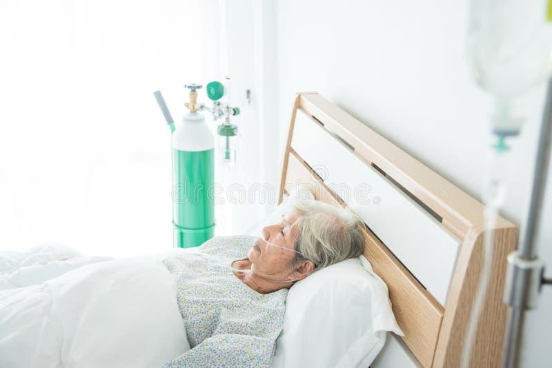 Paziente femminile senior che dorme sul letto in ospedale immagini stock