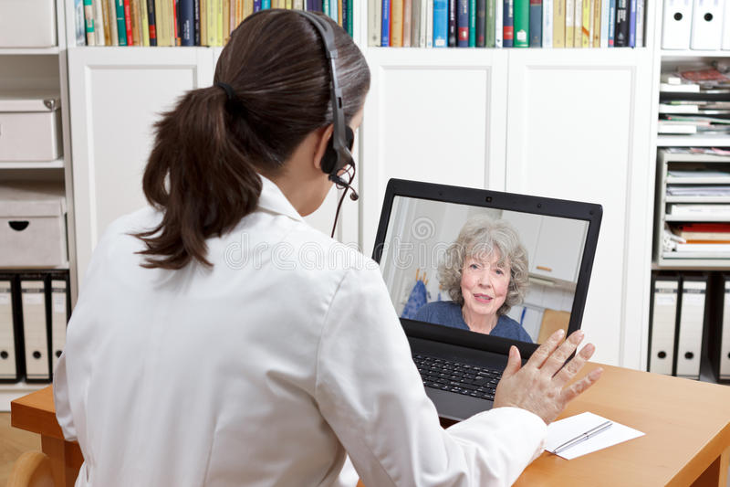 Paziente geriatrico del computer portatile della cuffia avricolare di medico immagine stock libera da diritti