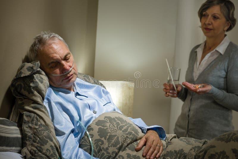 Paziente maschio anziano malato e moglie preoccupantesi immagine stock