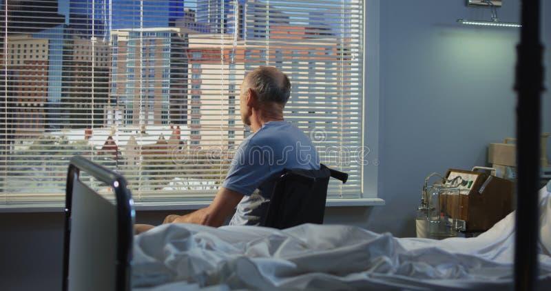 Paziente maschio anziano in ospedale vicino alla finestra immagini stock