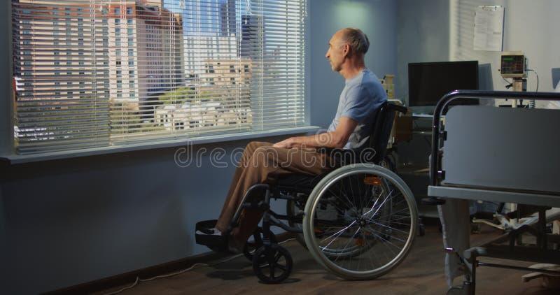 Paziente maschio anziano in ospedale vicino alla finestra fotografia stock