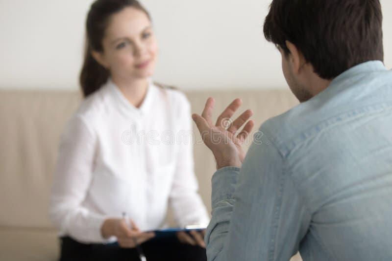 Paziente maschio consultantesi dello psicologo femminile, intervista di lavoro, busi immagine stock libera da diritti