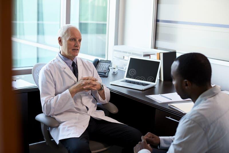 Paziente maschio del dottore In Consultation With in ufficio fotografia stock
