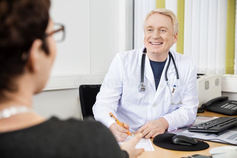 Paziente maschio del dottore Looking At Female allo scrittorio immagine stock