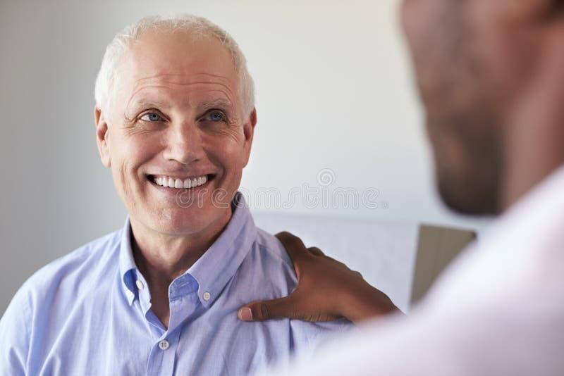 Paziente maschio del dottore Meeting With Mature nella stanza dell'esame fotografia stock libera da diritti