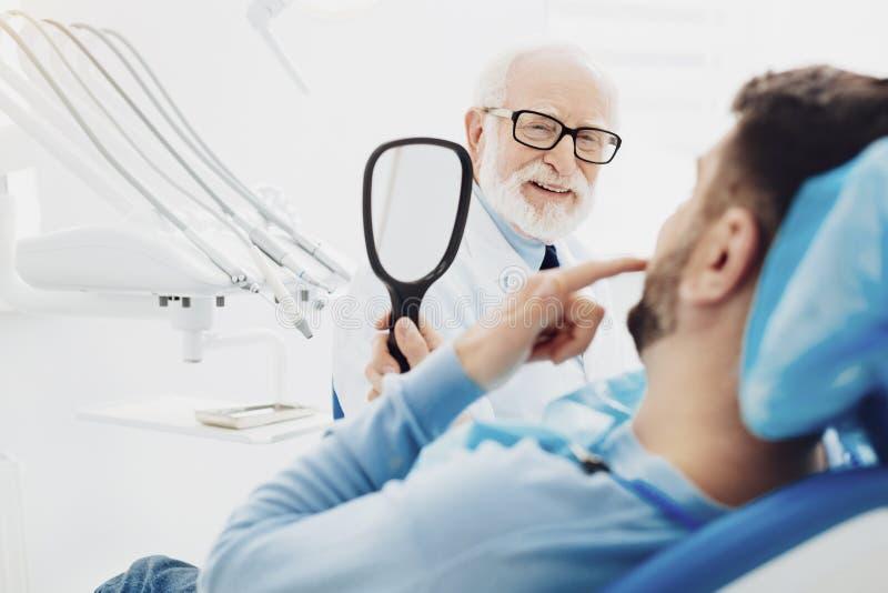 Paziente maschio felice che esamina i suoi denti immagine stock
