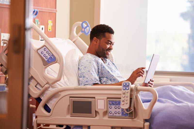 Paziente maschio nel letto di ospedale facendo uso della compressa di Digital immagini stock libere da diritti