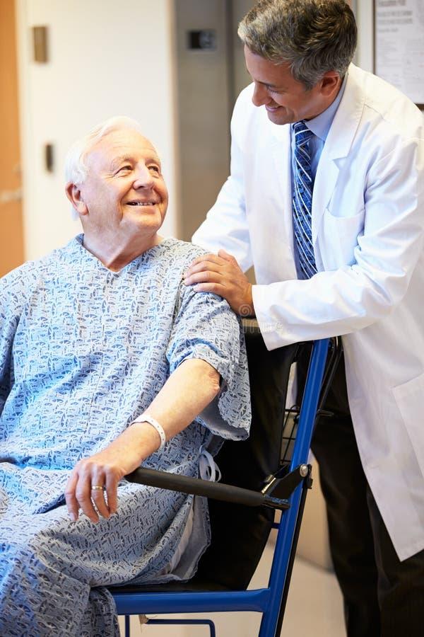 Paziente maschio senior che è inserito la sedia a rotelle da medico fotografia stock