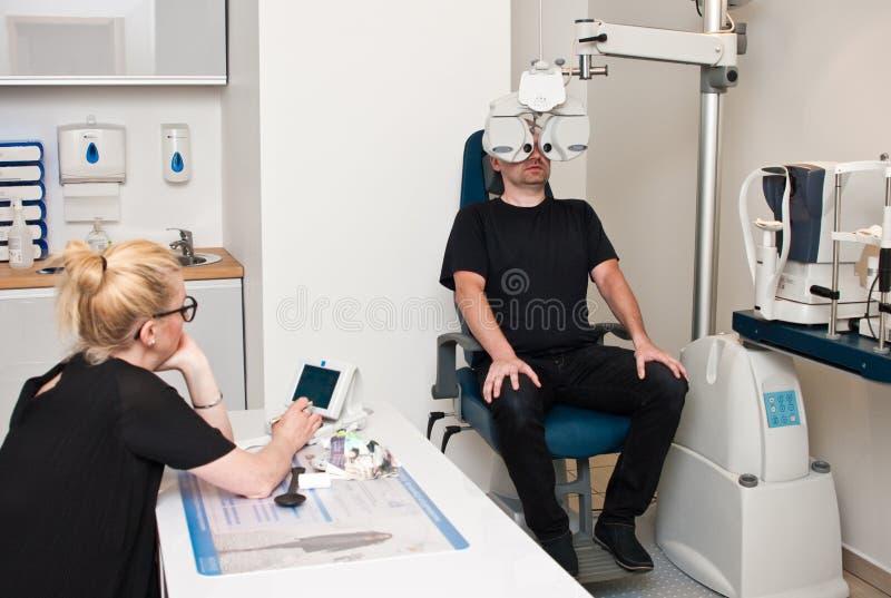 Paziente nell'ufficio dell'optometrista per esame degli occhi fotografia stock libera da diritti